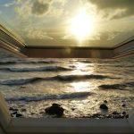 Blick durch ein Fenster auf Meer und Sonnenhimmel