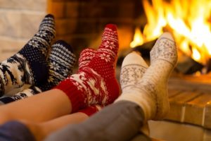 Füße mit Socken vor dem Kaminfeuer.