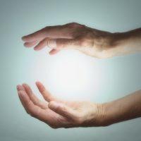 Energie-Lichtkugel zwischen zwei Händen