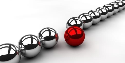 Rote Kugel rollt aus einer Reihe silberner Kugeln heraus