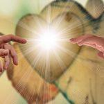 Begegnung zweier Hände vor Herzen