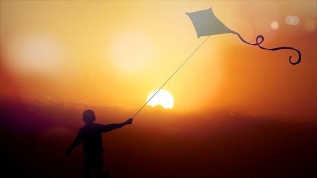 Drachen steigen lassen vor der untergehenden Sonne